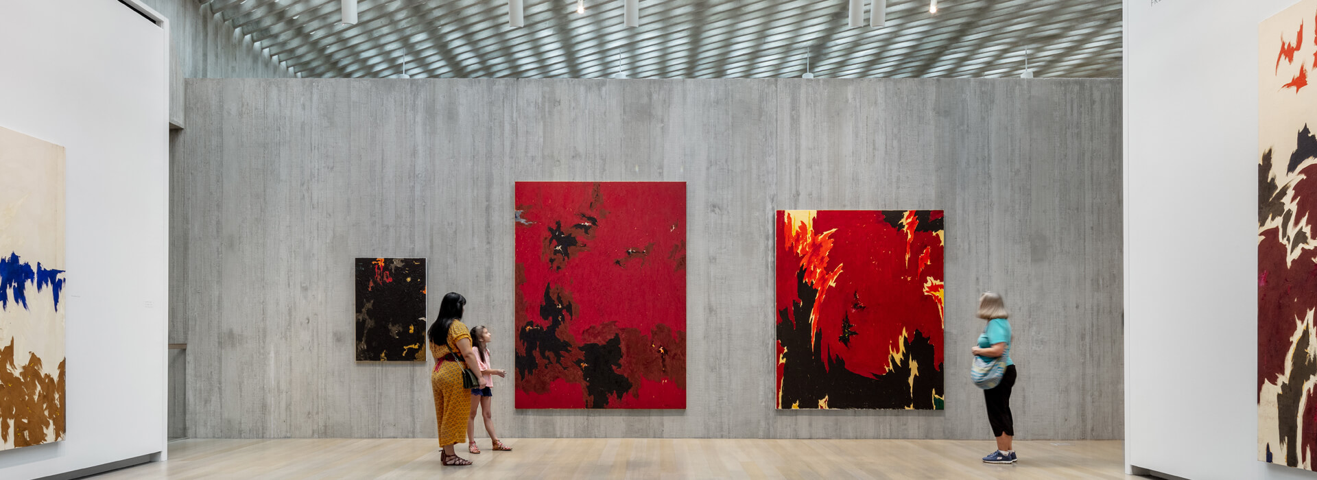 Woman and her daughter and another woman look at art in a large open gallery at the Clyfford Still Museum