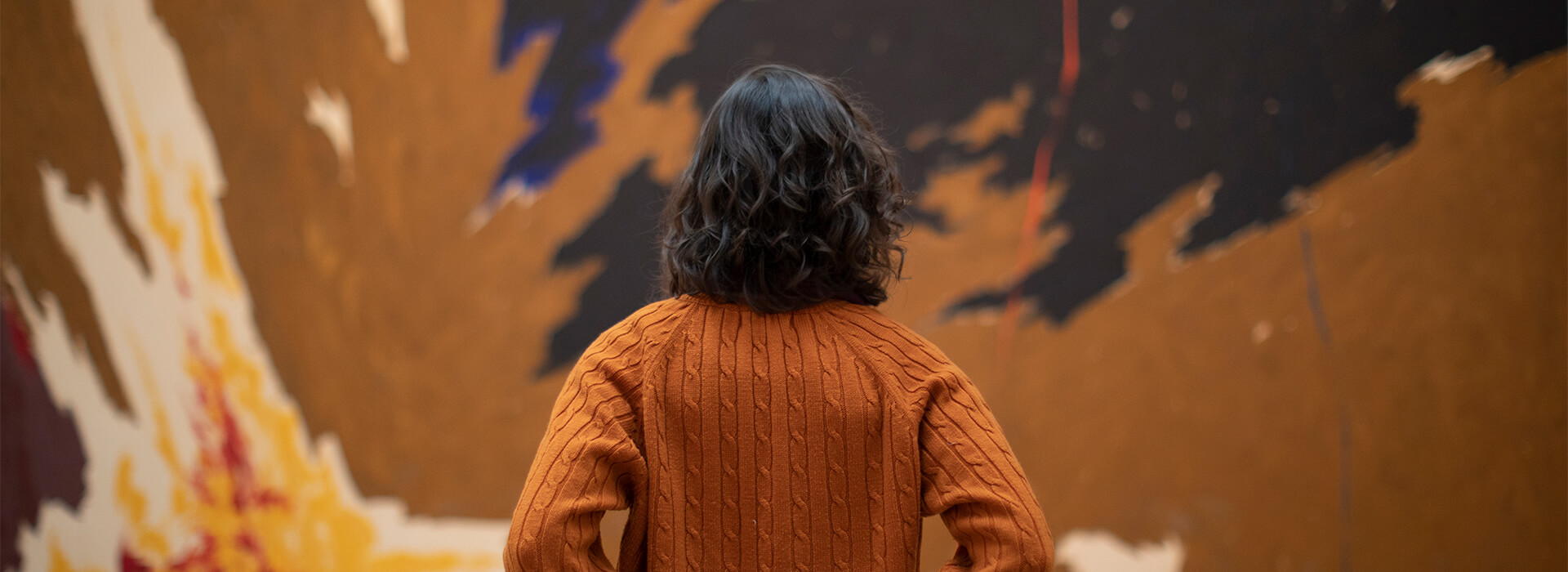 Woman wearing an orange sweater looks up at a large abstract painting with brown, yellow red, blue, black, and orange paint