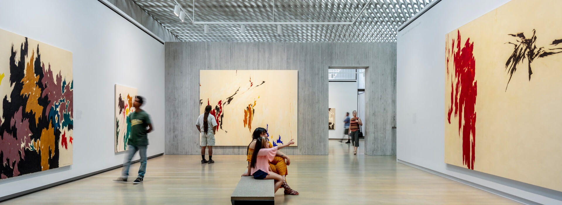 A mom and daughter sit on a bench while two men stand on the other side of the room looking at art