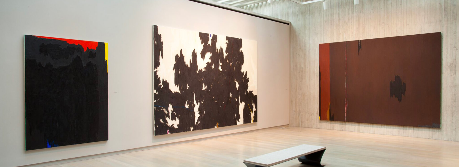 Three large abstract oil paintings hang on the walls of the Clyfford Still Museum