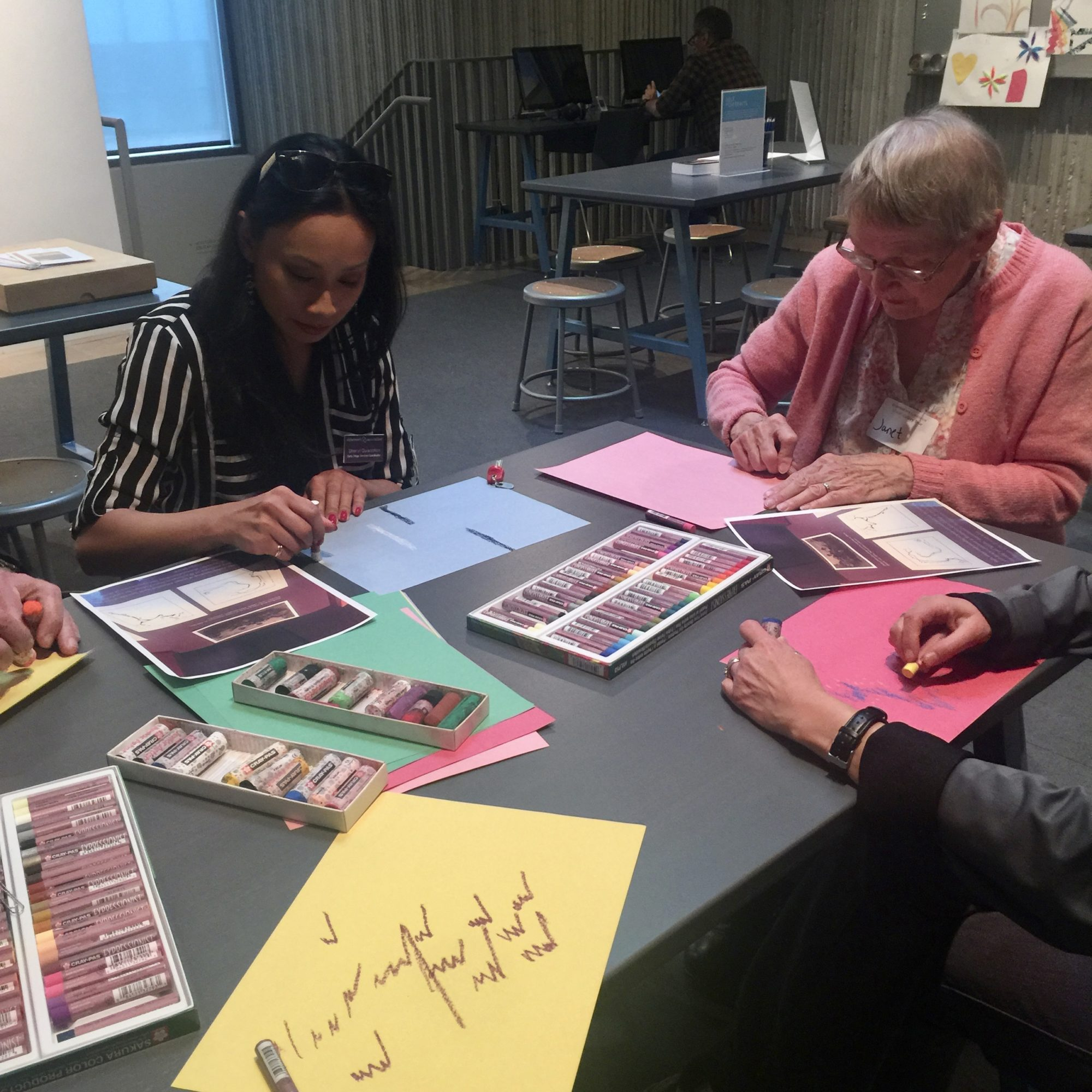 A group of women sit at a table a color on different pages of construction paper with pastels
