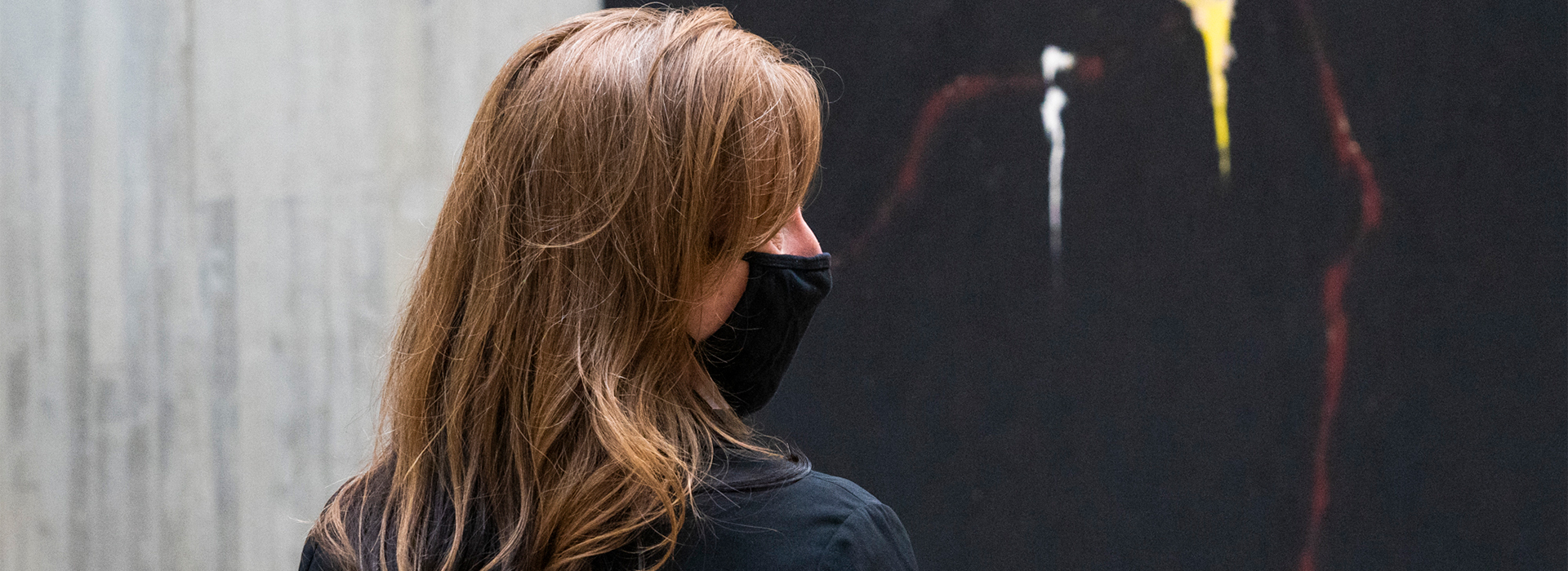 Side profile photo of a woman wearing a mask standing in front of a mostly black abstract painting by Clyfford Still