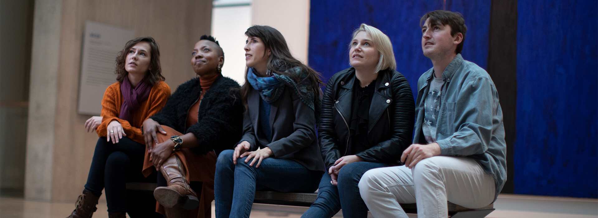 A group sits on a bench looking at art and talking about it