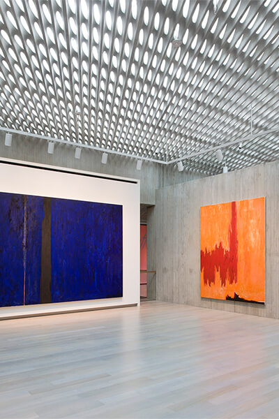 Empty gallery space with large colorful abstract paintings on the walls