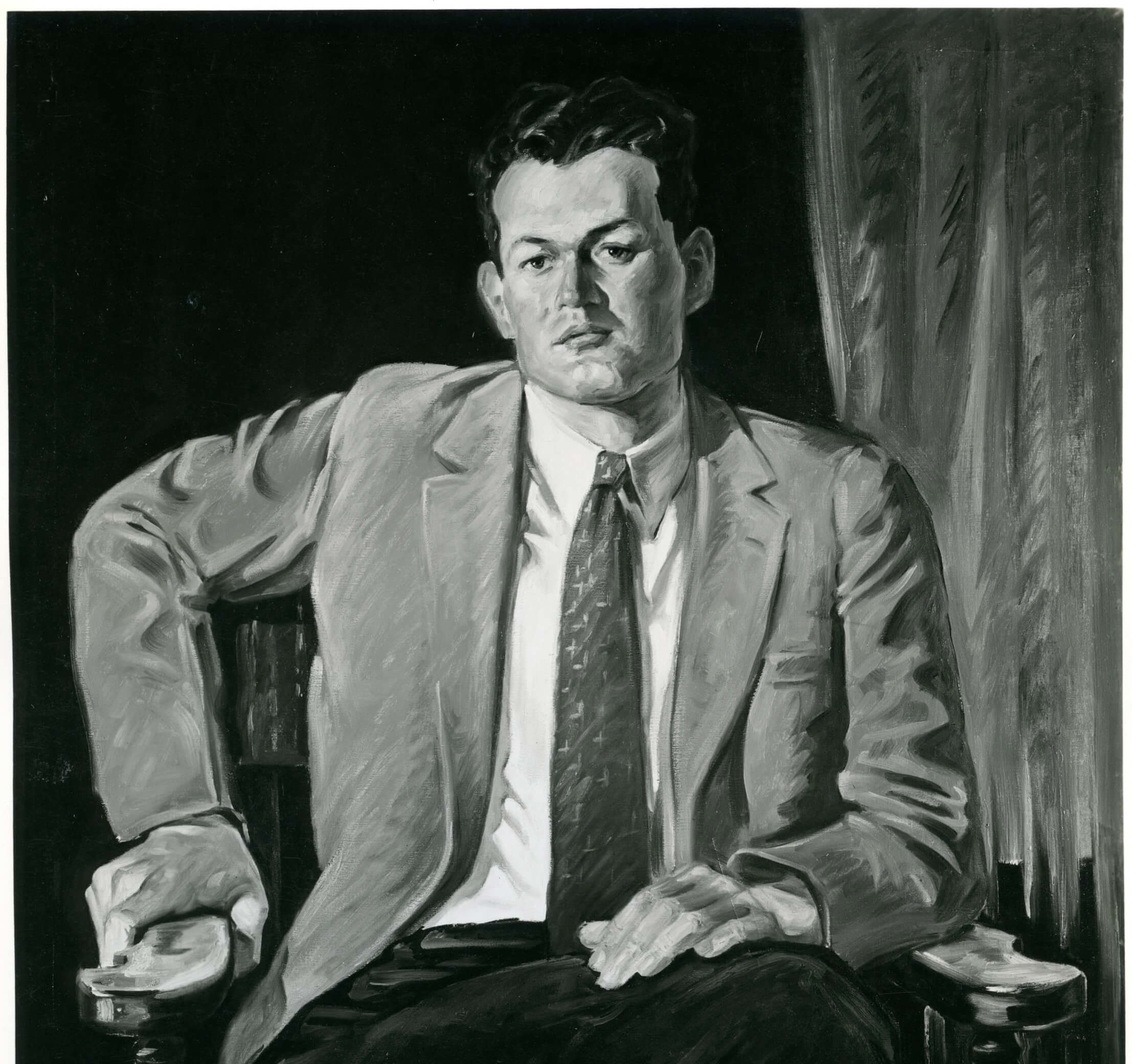 Portrait of a man with his jacket open, wearing a tie, and with one arm bent at a 90 degree angle to the side