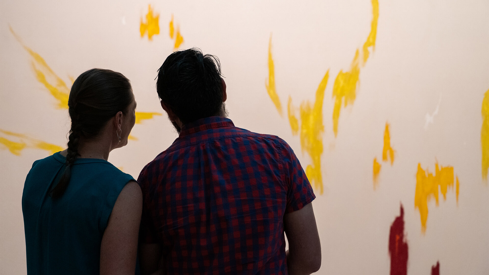A husband and wife lean into each other and look at a painting in a dark art gallery