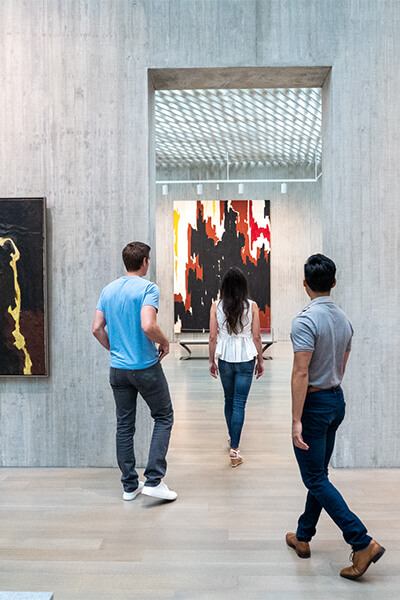 Two men and a woman walk through the concrete opening between two galleries at the Clyfford Still Museum